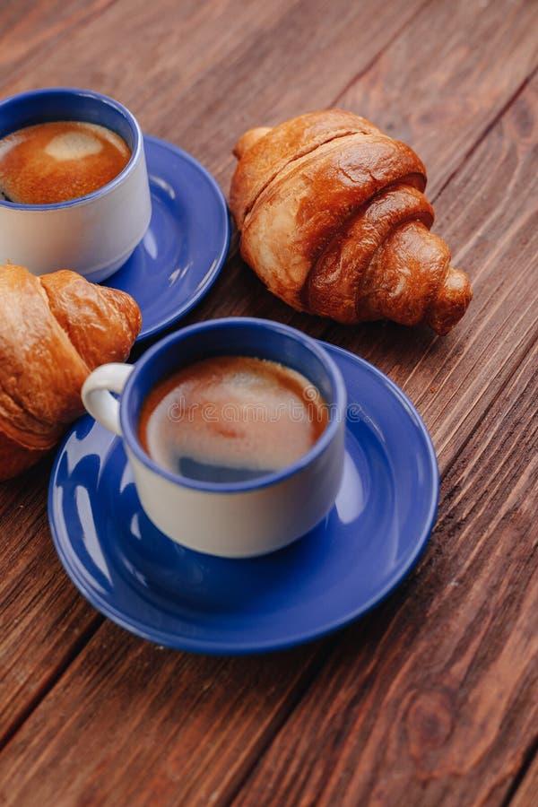 Dwie filiżanki kawy i kroissantów na drewnianym tle, dobre światło, poranna atmosfera obraz royalty free