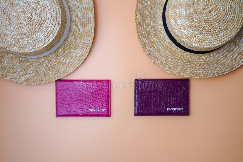 Dwie kobiece kapelusze ze słomki na plaży, paszporty na tle beżowym Koncepcja podróży, podróży i turystyki zdjęcie royalty free