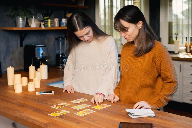 Dwie młode kobiety bawiące się kartami tarota w kuchni Widoczne świece i telefony komórkowe obraz stock