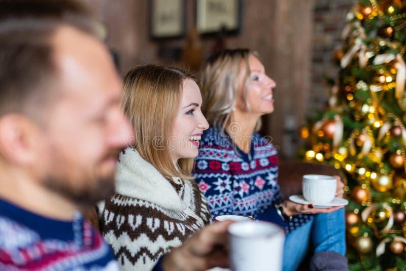 Dwie młode kobiety i mężczyzna uśmiechają się pijąc kawę siedząc przy choince obrazy royalty free