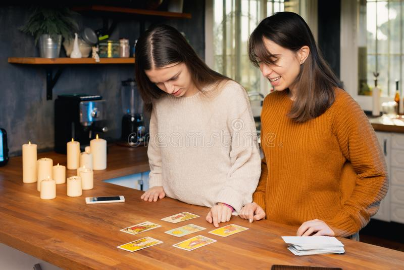 Dwie młode kobiety martwią się o znaczenie kartek z tarot granych w kuchni obrazy royalty free