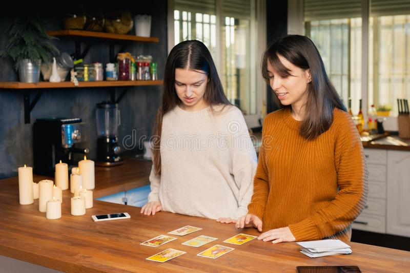 Dwie młode kobiety zdenerwowane używaniem kart tarota w kuchni rodzinnej obraz stock