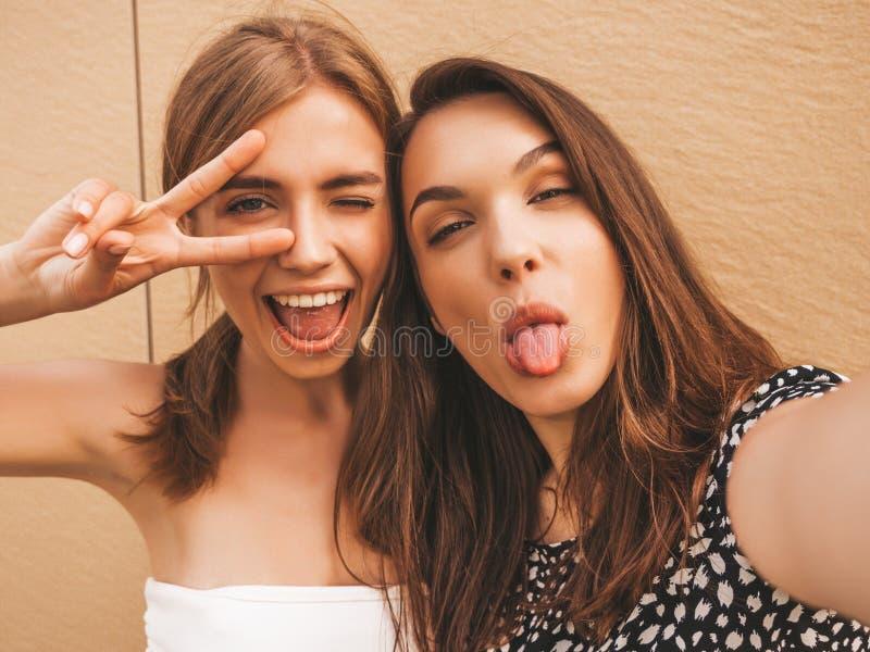 Dwie młode, piękne, uśmiechnięte histerny w modnych, letnich ubraniach obraz stock