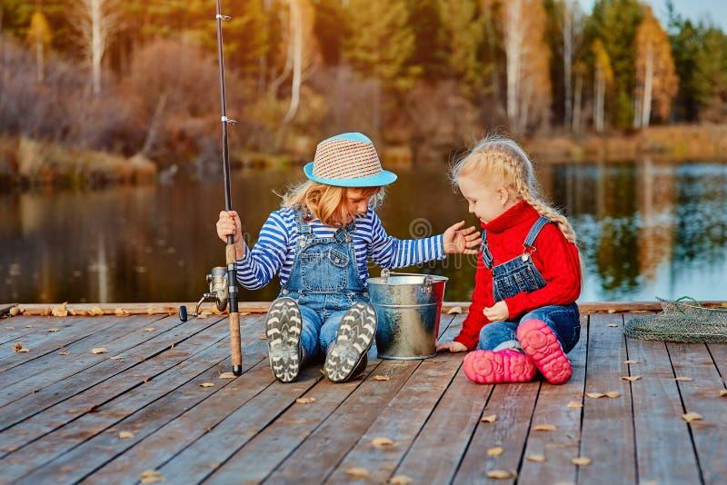 Dwie małe siostry lub przyjaciółki siedzą z wędkami na drewnianym molo Złapali rybę i włożyli do wiadra Są szczęśliwi. zdjęcie royalty free