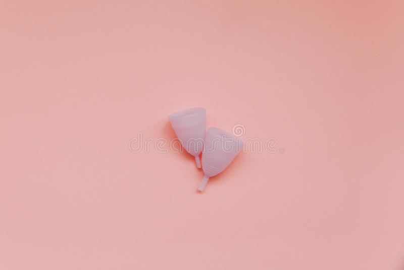 Dwie menstruacyjne kubki na jasnoróżowym tle Alternatywny produkt higieniczny dla kobiet w tym okresie Koncepcja zdrowia kobiet K fotografia royalty free