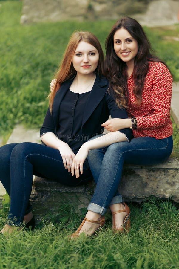 Dwie stylowe szczęśliwe kobiety przytulające się do parku w europie, szczere chwile przyjaźni obraz stock