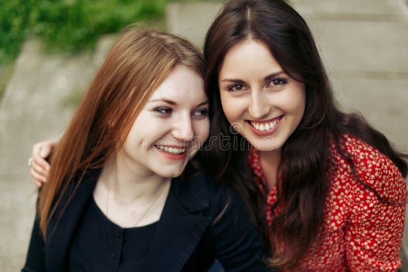 Dwie stylowe szczęśliwe kobiety przytulające się do parku w europie, szczere chwile przyjaźni zdjęcia royalty free