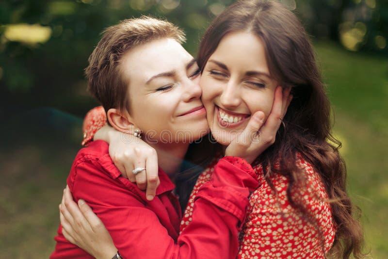 Dwie stylowe szczęśliwe kobiety przytulające się i uśmiechające się w parku miast europy, szczere chwile koncepcja przyjaźni zdjęcie royalty free