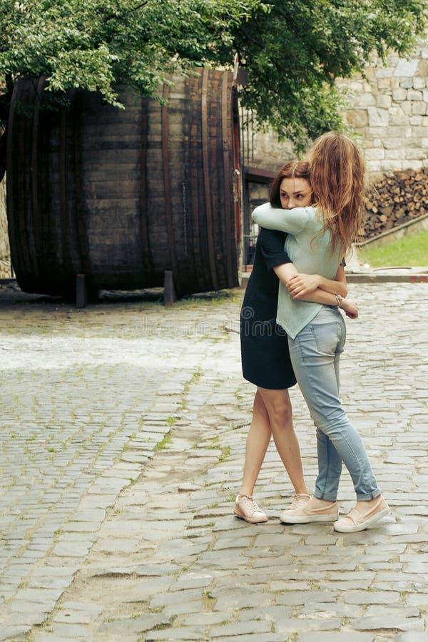 Dwie stylowe, wesołe kobiety hipsterzy przytulające się na ulicy w europie, szczere chwile koncepcja przyjaźni zdjęcie royalty free