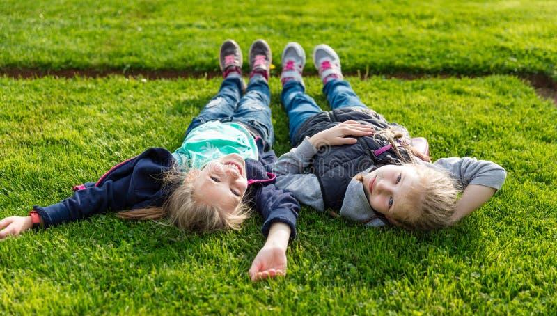 Dwie uśmiechnięte dzieci leżące na trawie fotografia royalty free