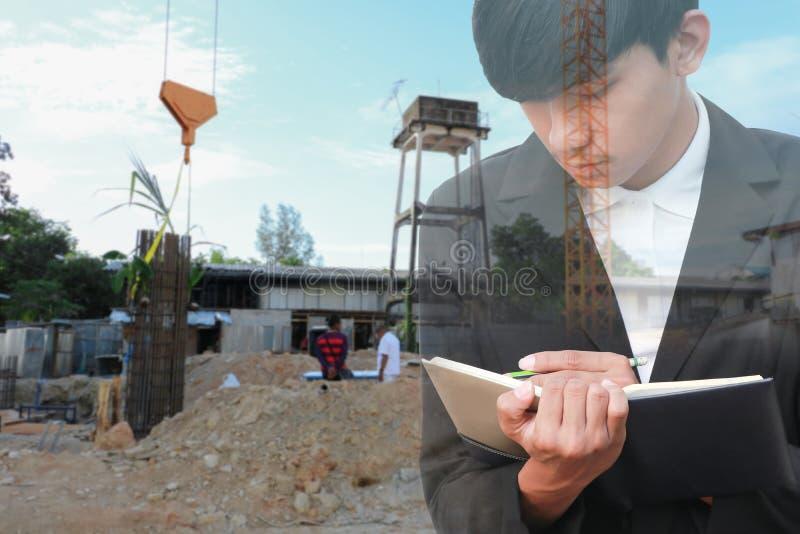 Dwoistego ujawnienia biznesmen z notepad w ręki podpisywania dokumentach w budowy miejscu pracy obraz royalty free