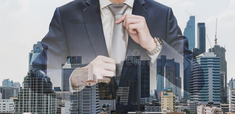 Dwoistego ujawnienia biznesmena mienia szyi krawat z nowożytnymi budynkami w Bangkok miasta tle obrazy stock
