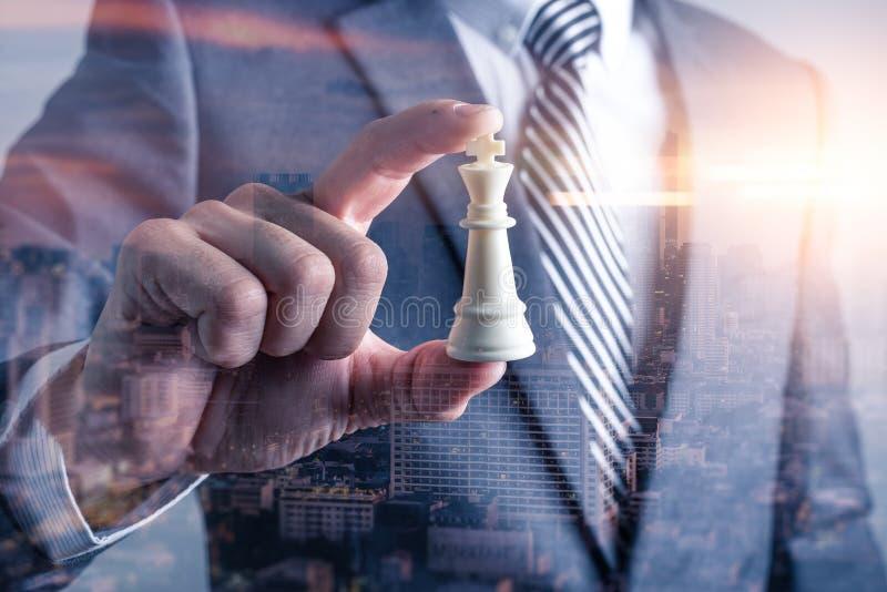 Dwoistego ujawnienia wizerunek biznesmena chwyt szachowy królewiątko na ręki narzucie z pejzażu miejskiego wizerunkiem fotografia stock