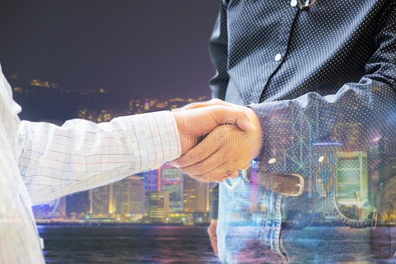 Dwoisty biznesowego mężczyzna i partnera uścisk dłoni z Hong kong nocą c zdjęcia royalty free
