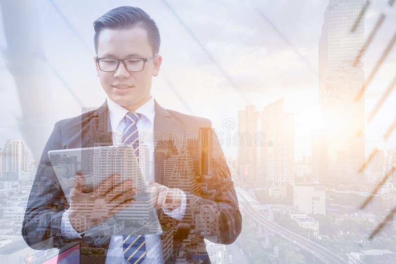 Dwoisty ujawnienie biznesmen ubierał w czarnym kostiumu używać cyfrową pastylkę z panoramicznym nowożytnym miasto widokiem Techno zdjęcie royalty free