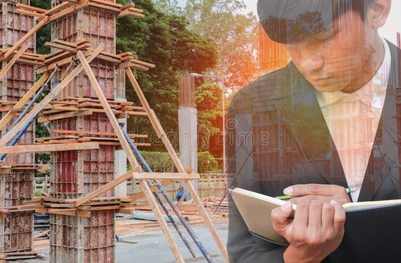 Dwoisty ujawnienie biznesmen z notepad w ręki podpisywania dokumentach w budowy miejsca pracy pojęciu zdjęcie stock