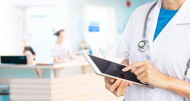 Dwoisty ujawnienie Doktorska mienie pastylka z stetoskopem na zamazanym szpitalnym tle fotografia royalty free