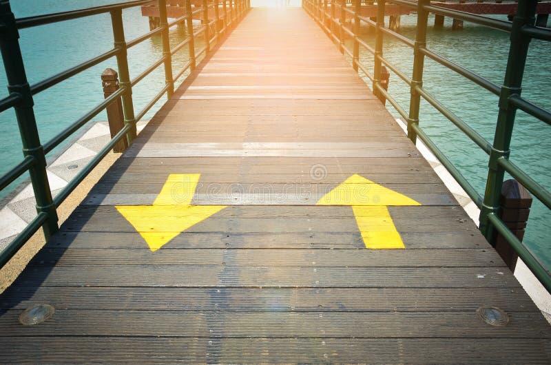 Dwudrogowych żółtych ruch drogowy strzał szyldowy wskazywać dwa kierunek na drewnianym moście fotografia royalty free