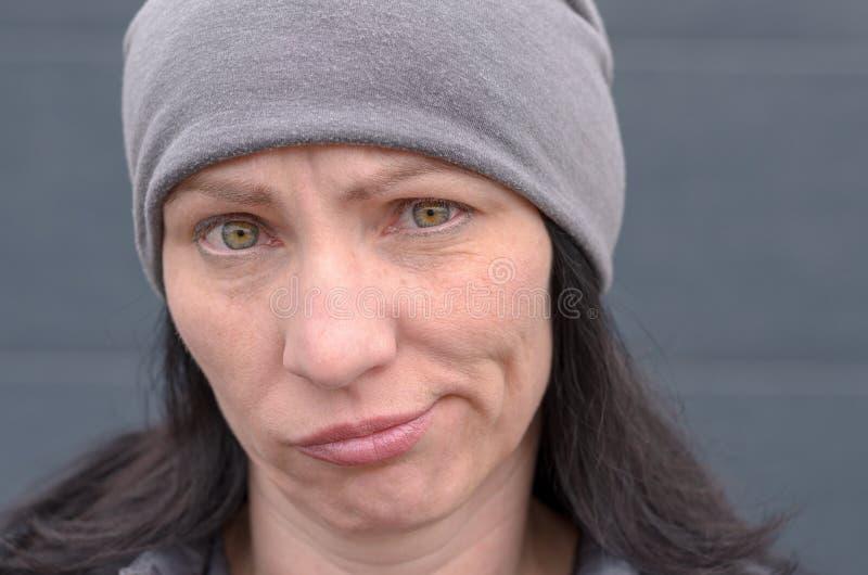 Dwuznaczna kobieta grimacing i patrzeje kamerę obraz royalty free
