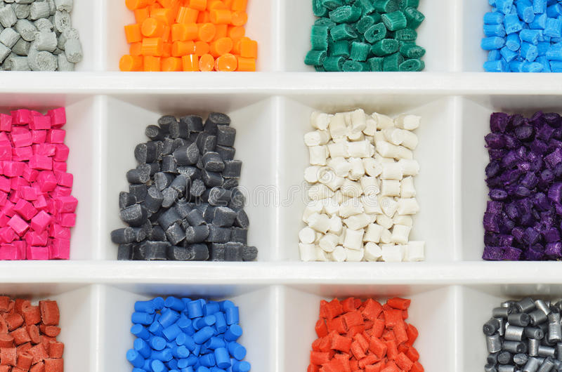 Dyed polymer. Several dyed polymer resin batches in boxes in laboratory stock photo