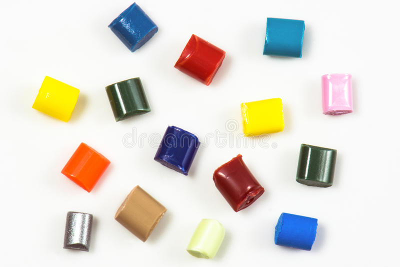 15 dyed polymer resins. Fifteen different dyed polymer pellets on white royalty free stock image