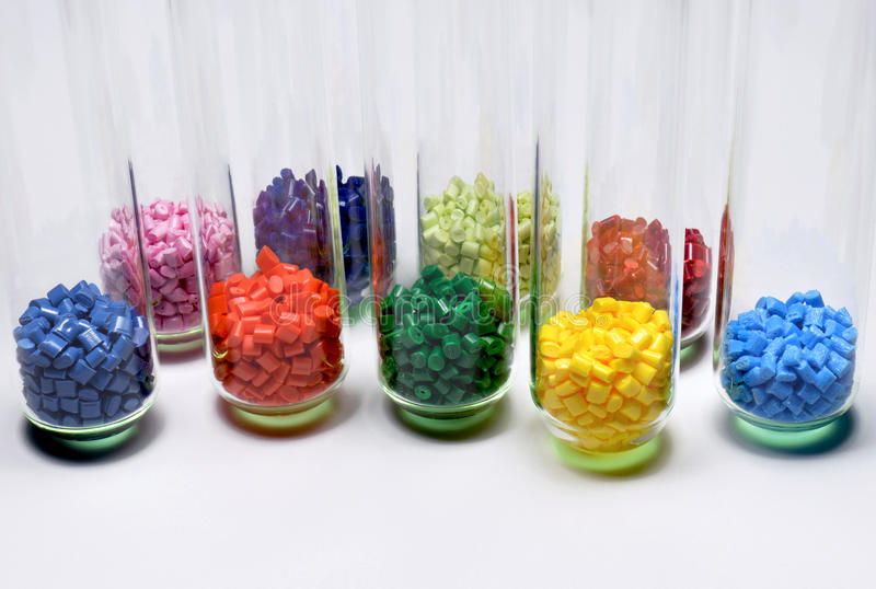 Dyed polymer in test glasses. Several dyed polymer resins in test glasses in laboratory stock images