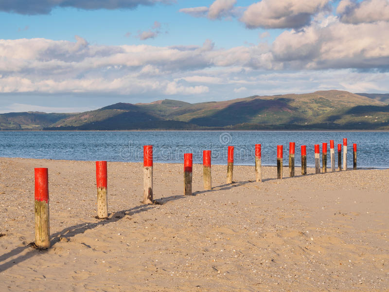 Dyfi Estuary and Clouds. Colourful marker posts and estuary at Ynyslas at the head of the Dyfi Dovey estuary just north of Borth, Ceredigion, Wales royalty free stock image