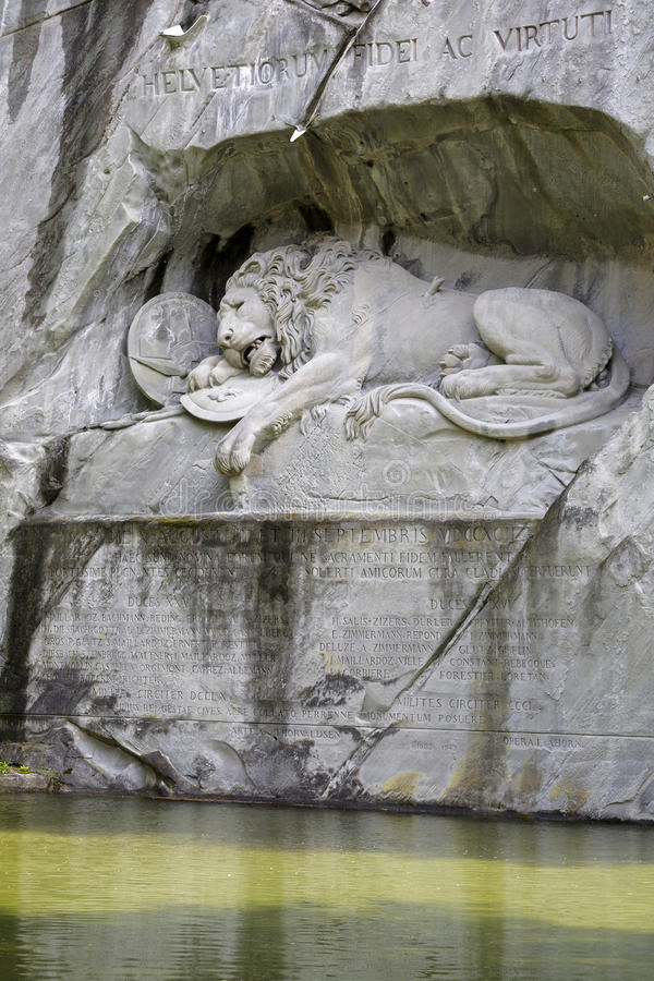 Dying Lion carved in rocky wall stock images