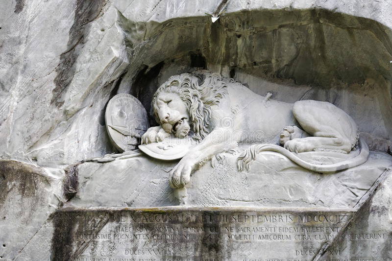 Dying Lion carved in rocky wall royalty free stock image