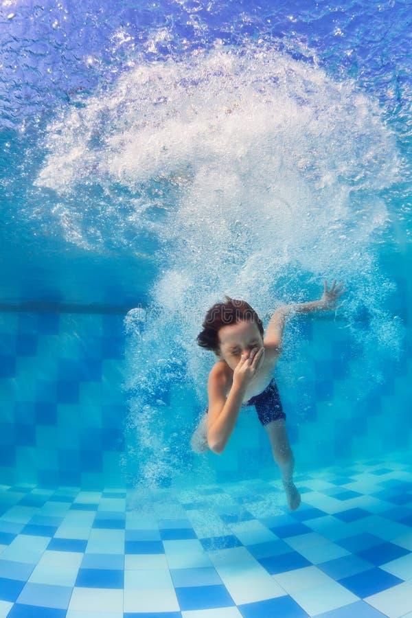 Dyka för barn som är undervattens- i simbassäng royaltyfri bild
