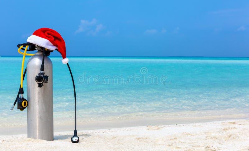 Dykapparatbehållare och regulator med julhatten på tropisk inställning royaltyfri fotografi