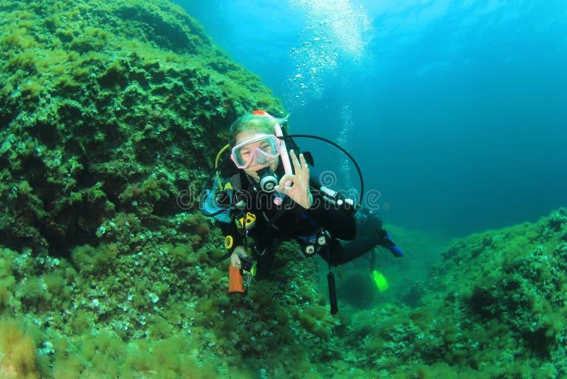 Dykapparatdykning för ung kvinna royaltyfria bilder