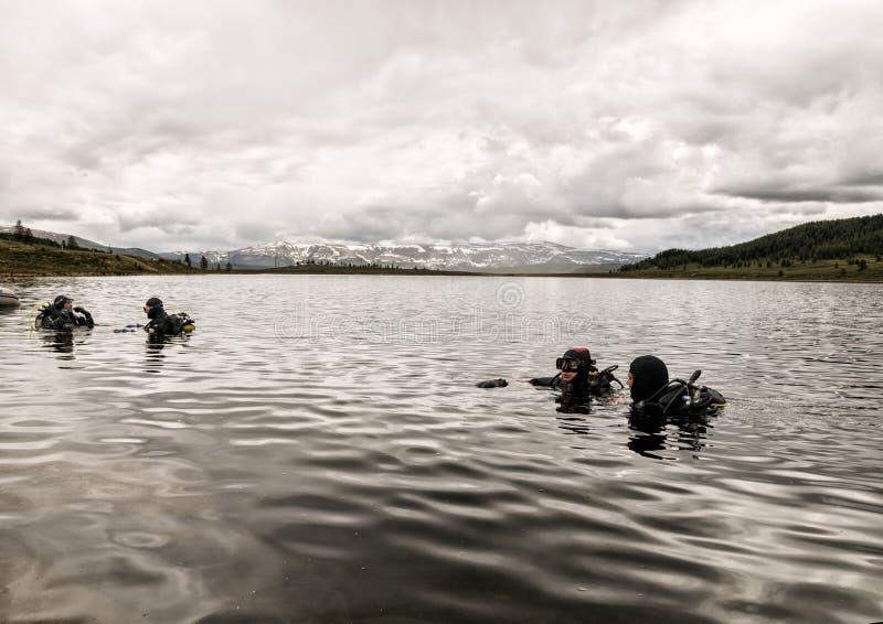 Dykapparatdykning i en bergsjö, övande tekniker för nöd- räddare immersion i kallt vatten fotografering för bildbyråer