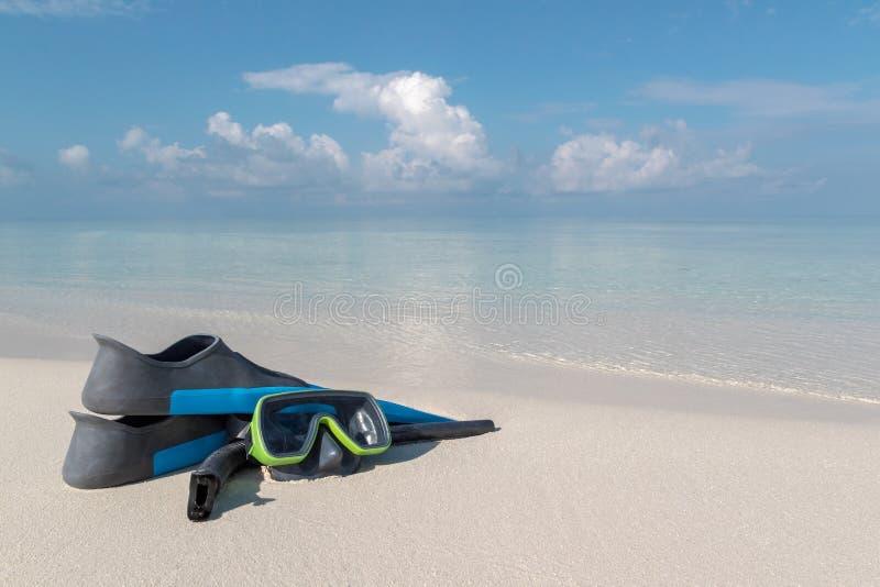 Dykapparatskyddsglasögon och flipper på en vit strand Klart blått vatten som bakgrund arkivbild