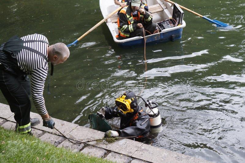 Dykare gör ren upp det Patriarshi dammet, Moskva royaltyfri bild