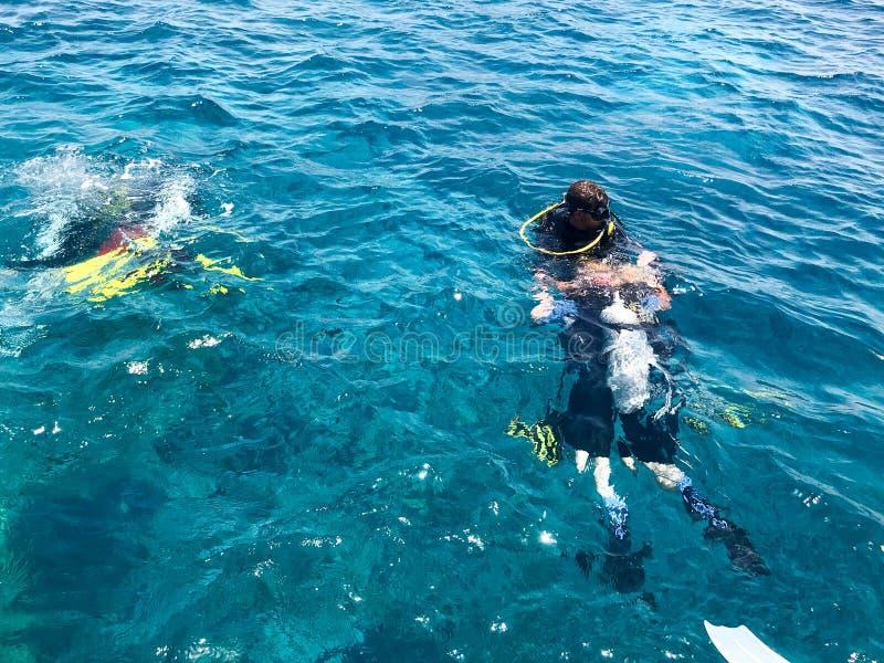 Dykare i vattentäta dräkter för svart dykning med aluminum kanistrar för skinande metall svävar, dyken in i klart havsvatten för  arkivfoto