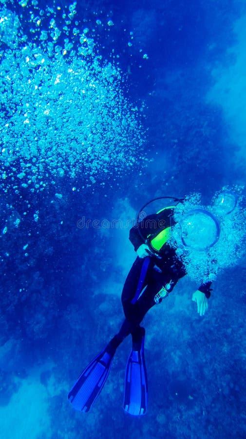 Dykaren producerar luftbubblor under vatten i blått vatten arkivfoton