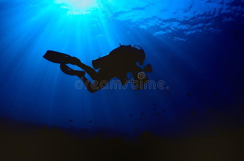 Dykares kontur, medan går ner in i det djupblått fotografering för bildbyråer