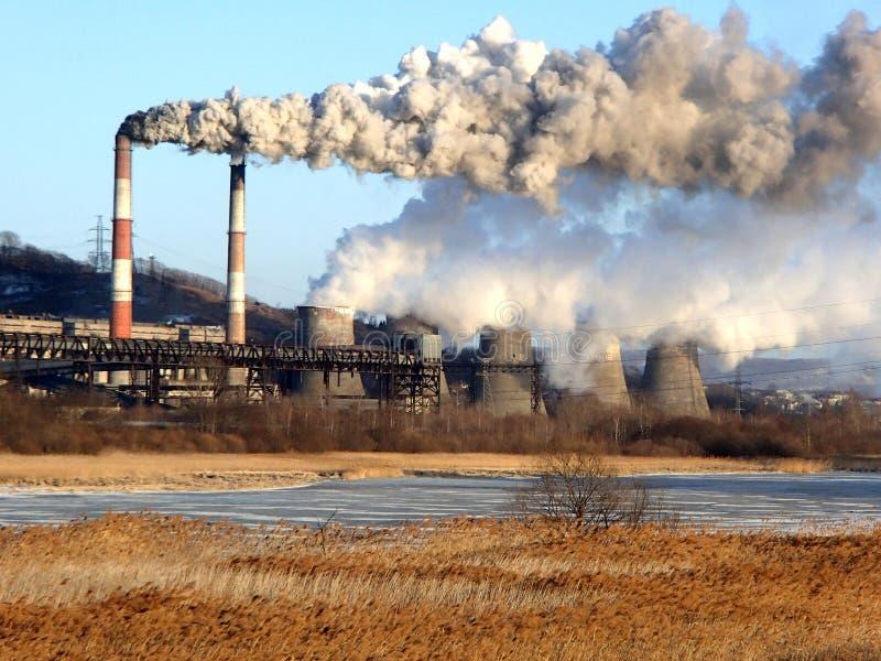 Dymienie drymby i wyparowywać cooler górują zasilanie elektryczne stacja nad zamarzniętą zimy rzeką obrazy stock