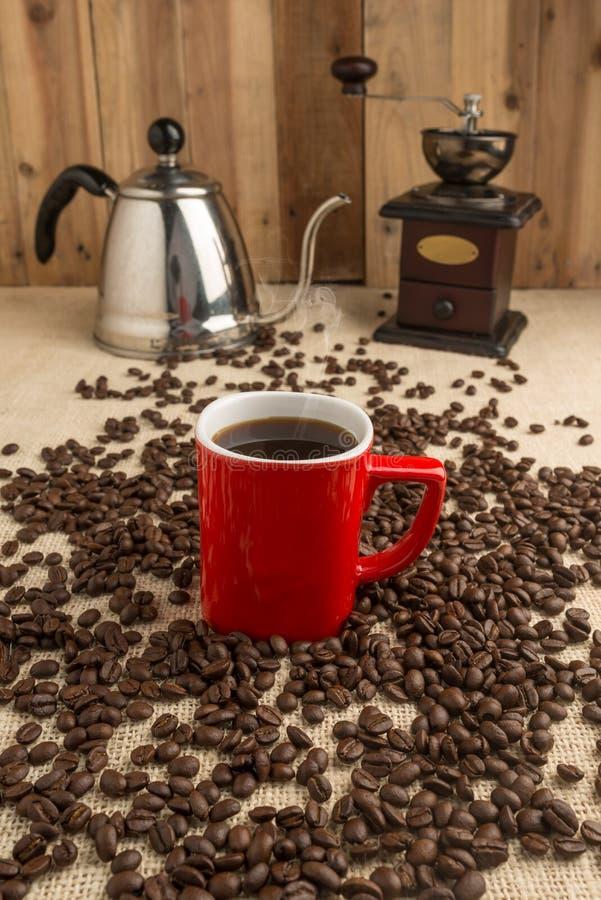 Dymienie kawa espresso w czerwonej filiżance z kawowymi fasolami mil i starą kawą obraz stock