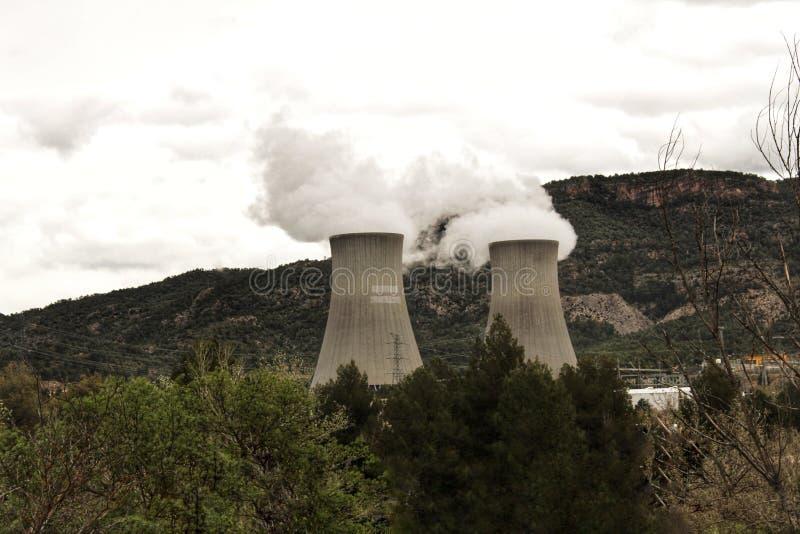 Dymienie kominy w elektrowni jądrowej między górami obraz stock