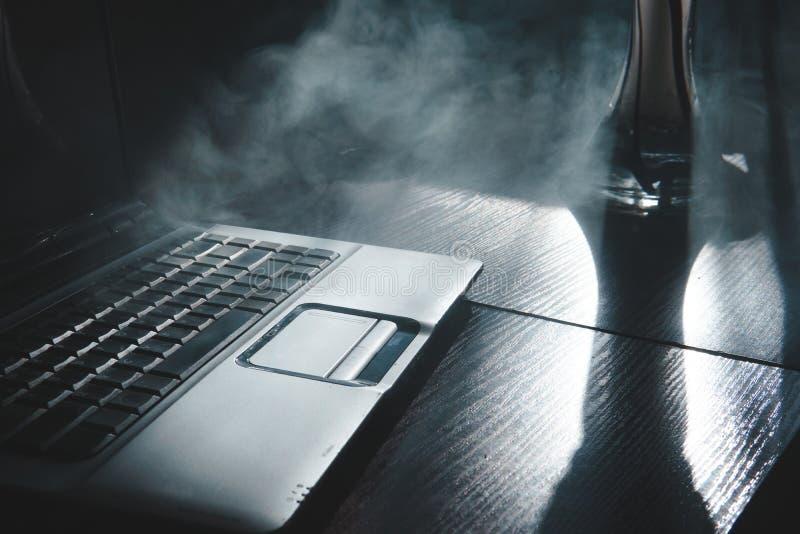 Dymienie nargile podczas gdy pracuj?cy na laptopie w domu, ciemny temat, zako?czenie w g?r?, s?o?ce lekkie linie obraz royalty free