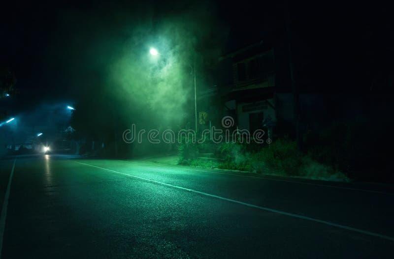 Dymna pobliska latarnia uliczna na jawnej drodze z starym zaniechanym domowym tłem w Trang Tajlandia Horror scena obraz stock
