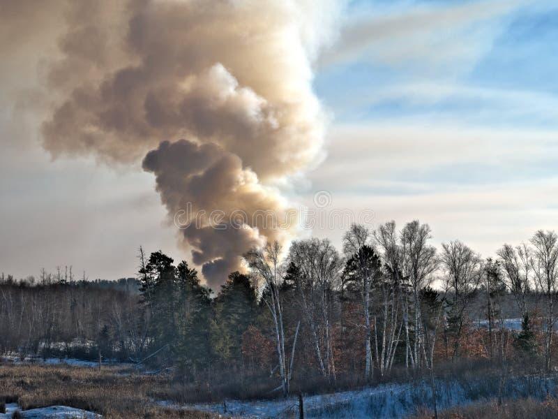 Dymny kłębić się od kontrolowanego ogienia przy wysypiska miejscem w zimie w Minnestoa zdjęcie royalty free