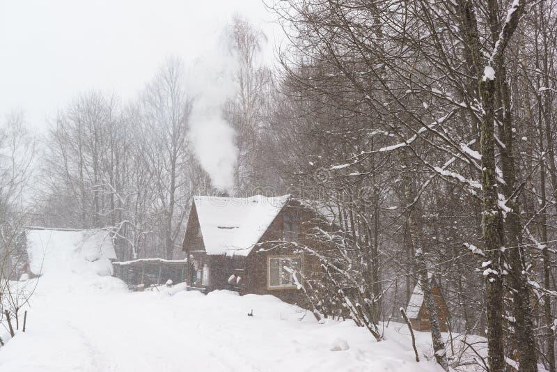 Dymu komes od kominu wiejski dom w śnieżnym lasowym Ciężkim śniegu w zima dniu obraz royalty free