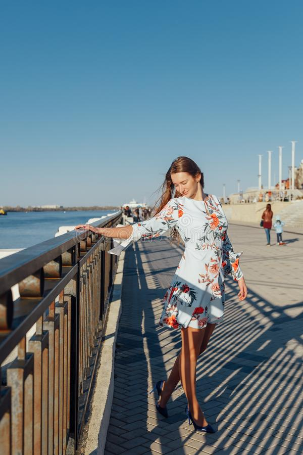 Dynamic fashion style Portrait of a young beautiful girl walking along the waterfront of the city royalty free stock photos