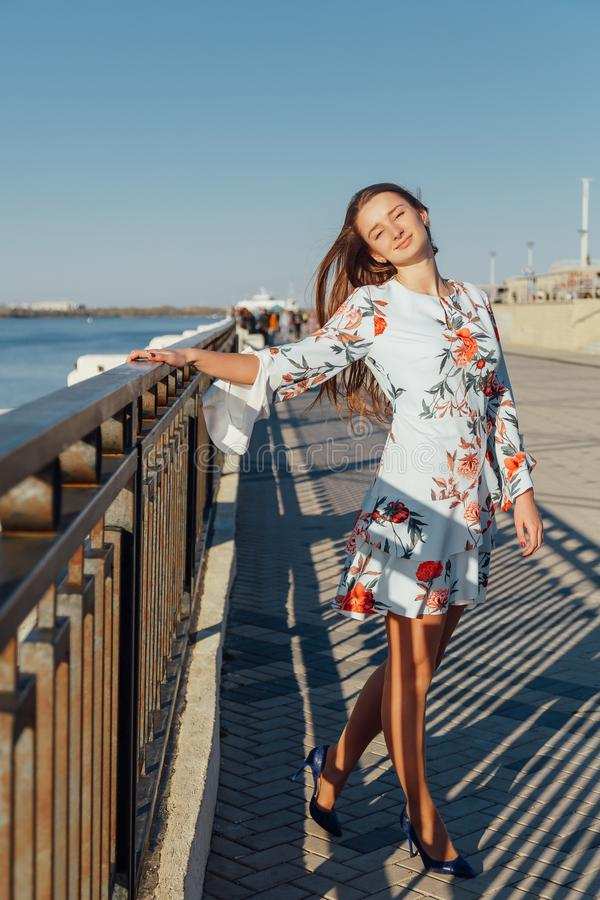 Dynamic fashion style Portrait of a young beautiful girl walking along the waterfront of the city stock photos