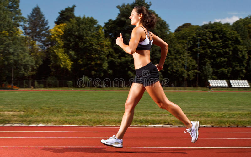 Dynamic image of a young woman running on a track royalty free stock images