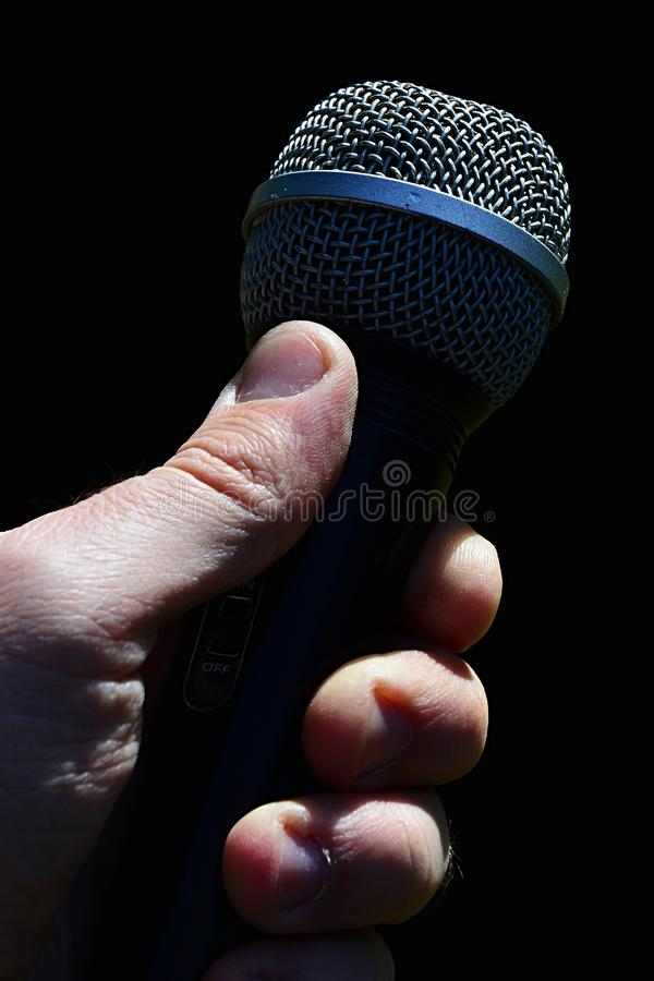 Dynamic professional microphone for vocal and instruments held in man left hand against dark background. Dynamic professional microphone for vocal and royalty free stock image