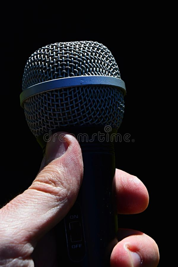 Dynamic professional microphone for vocal and instruments held in man left hand against dark background. Dynamic professional microphone for vocal and stock photography